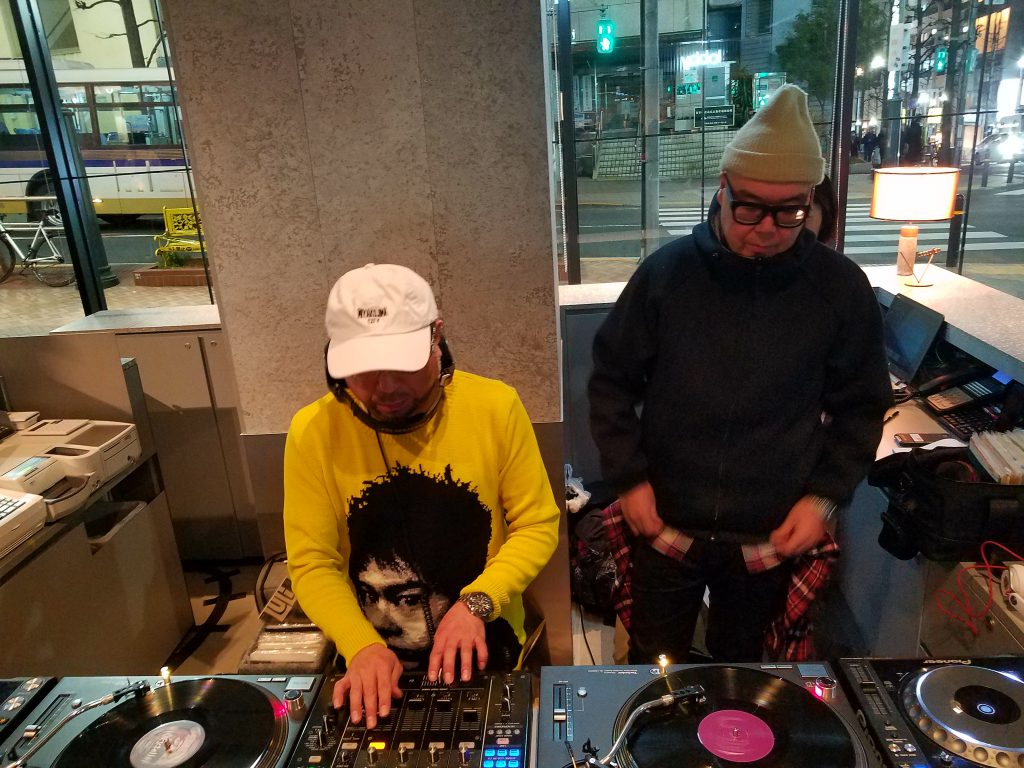 Tatsuo Sunaga on the decks, watched by FPM Tomoyuki Tanaka