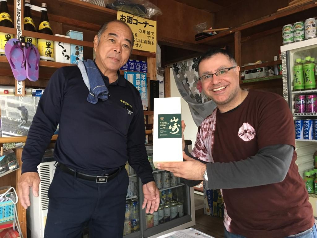 Mac and local Kakeromajima man with a bottle of 10-year Yamazaki off Amami Oshima