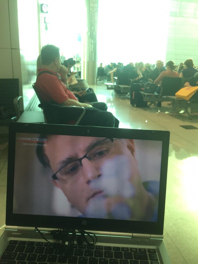 Chris watching NHK World'S Triangle Thrillers at Dubai Airport