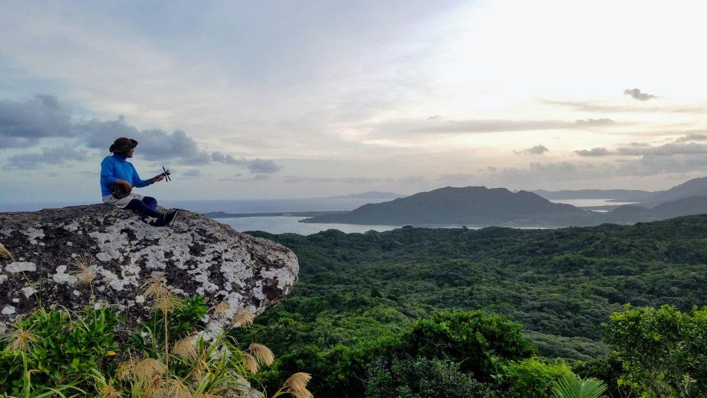Hiroshi playing sanshin at the summit of Mt. Yarabu-dake, Ishigaki Island